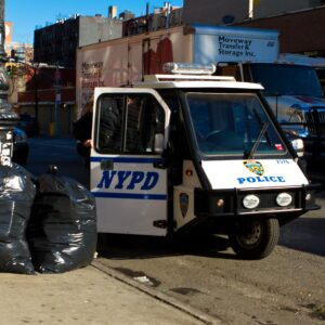 NYPD vehicle parked near garbage bags
