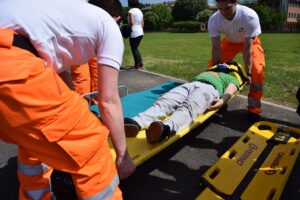 Two people rescuing a person on a stretcher