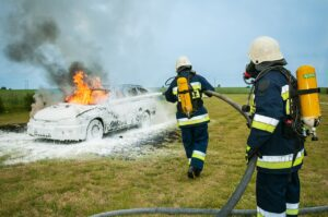Two firefighters extinguishing fire on a car