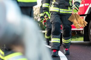 Three firefighters wearing uniforms and gloves
