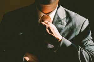 A person in a three-piece suit fixing the tie