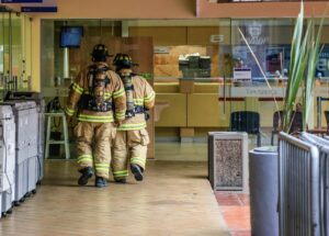 Two firefighters walking in the kitchen